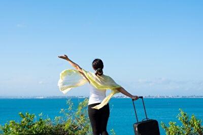 海 旅行鞄を持った女性
